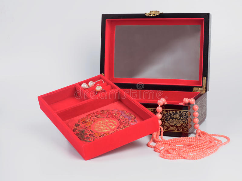 Jewel-box with coral bead necklace on white background. Picture of the opened jewel-box with red fit-out. Wooden jewel-box with pink coral bead necklace on stock photos