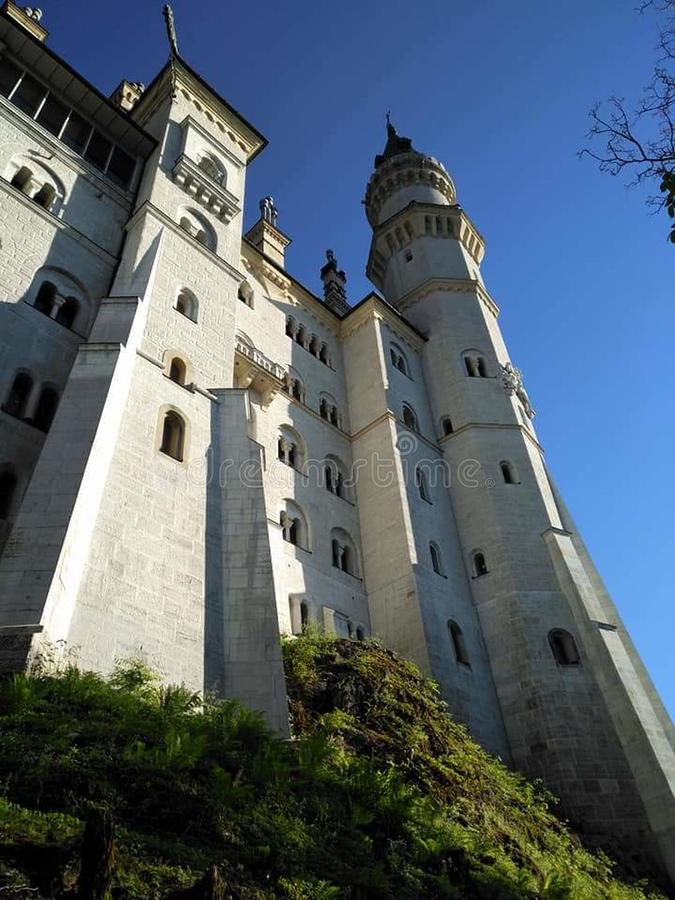 The jewel looms amazingly overhead. Castle Neu Schwanstein in Füssen Germany. A magnificent sight that almost bankrupted Bavaria royalty free stock image