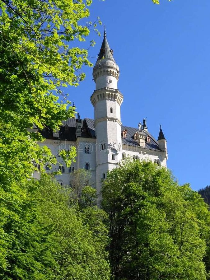 The jewel through the trees. Castle Neu Schwanstein in Füssen Germany. A magnificent sight that almost bankrupted Bavaria stock image