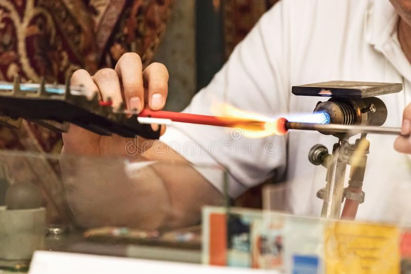 A jeweler artisan melting colored glass with a torch to make glass jewerly, Venice, Italy. A jeweler artisan melting colored glass with a torch to make glass royalty free stock photo