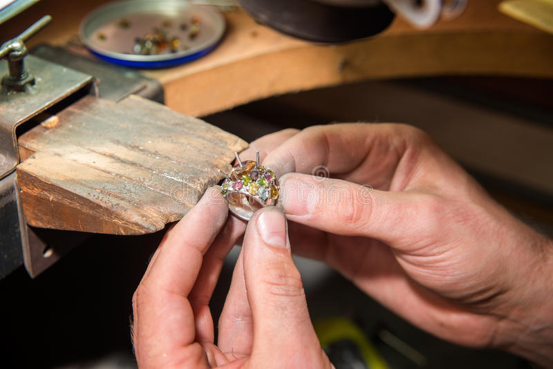 Jeweler fixes gems. On gold product royalty free stock photo