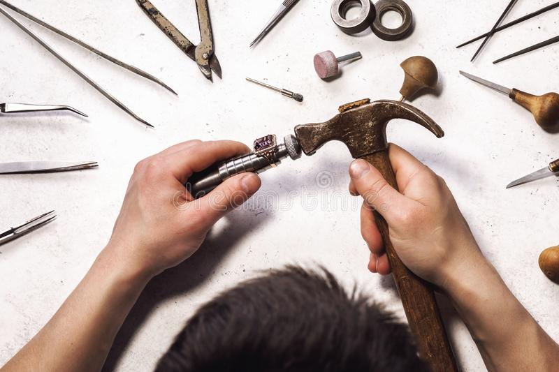 Jeweler increases the size of the gold ring at his workplace. Top view on the production process in the workshop royalty free stock photography