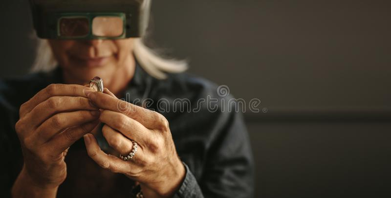 Jeweler inspecting diamond ring with magnifying glass stock photo