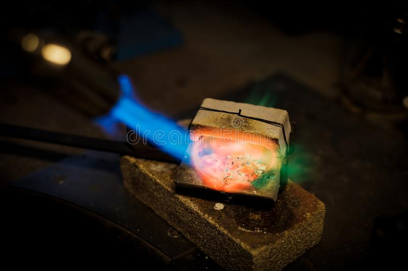 Jeweler melts with flame silver or gold on old workbench. Jeweler melts with a flame silver or gold on old workbench in jewelers workshop stock photography