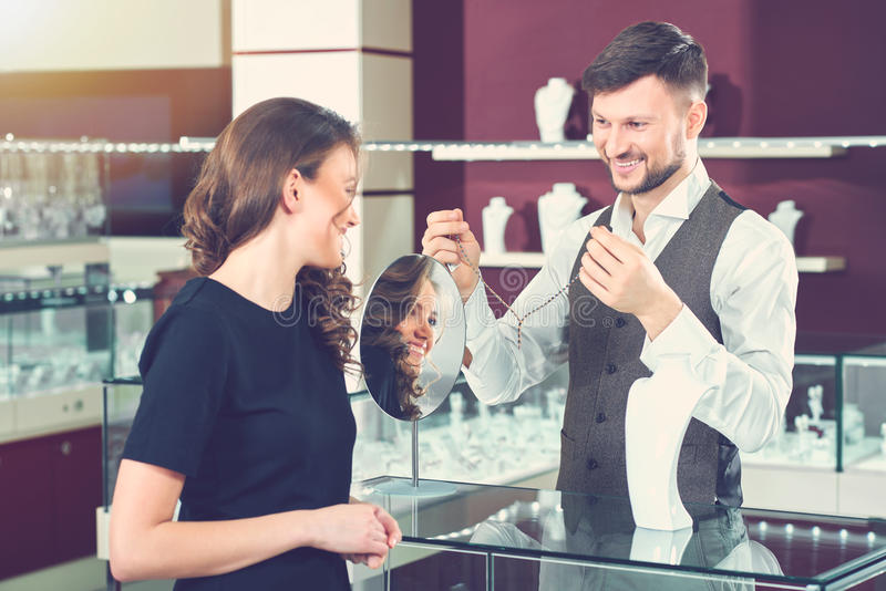 Jeweler showing golden necklace for buyer at store. stock photos