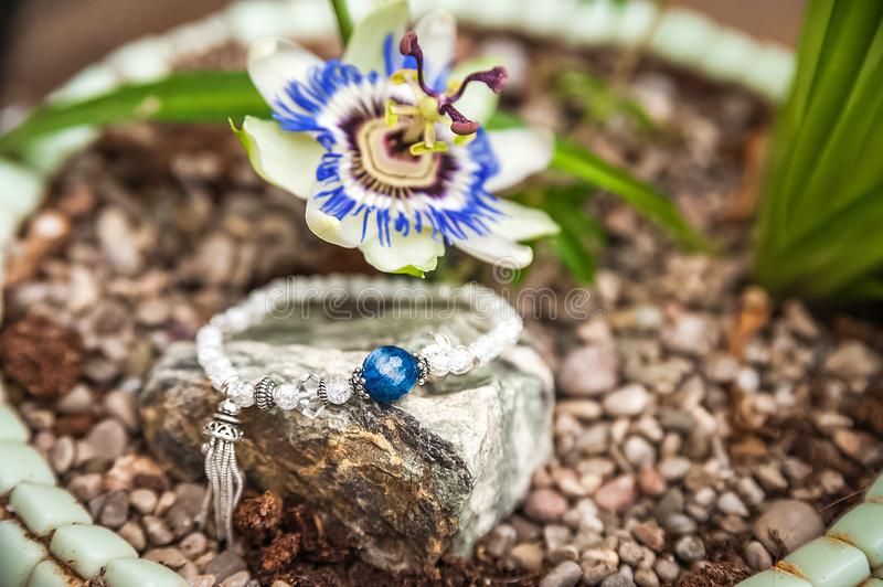 Jewelery made of natural stones against the backdrop of blossoming pasiflora. Bracelets, rings, necklaces, handmade earrings close stock photo