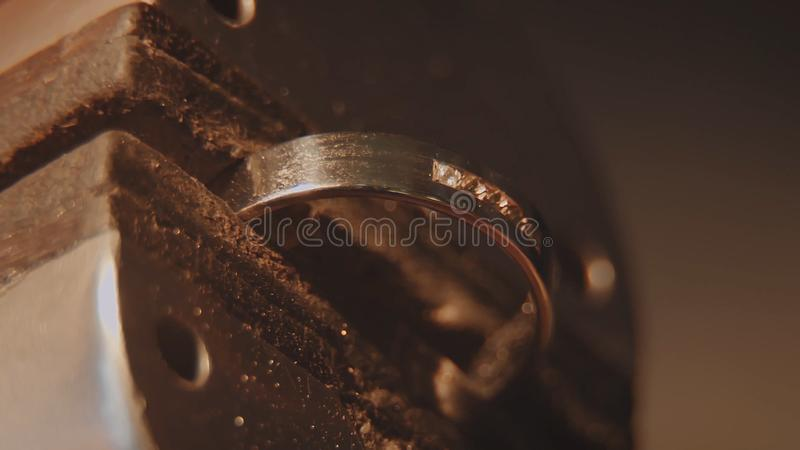 The jeweller is setting a precious stone. Craft jewelery making. Ring repairing. Putting the diamond on the ring. Macro royalty free stock images