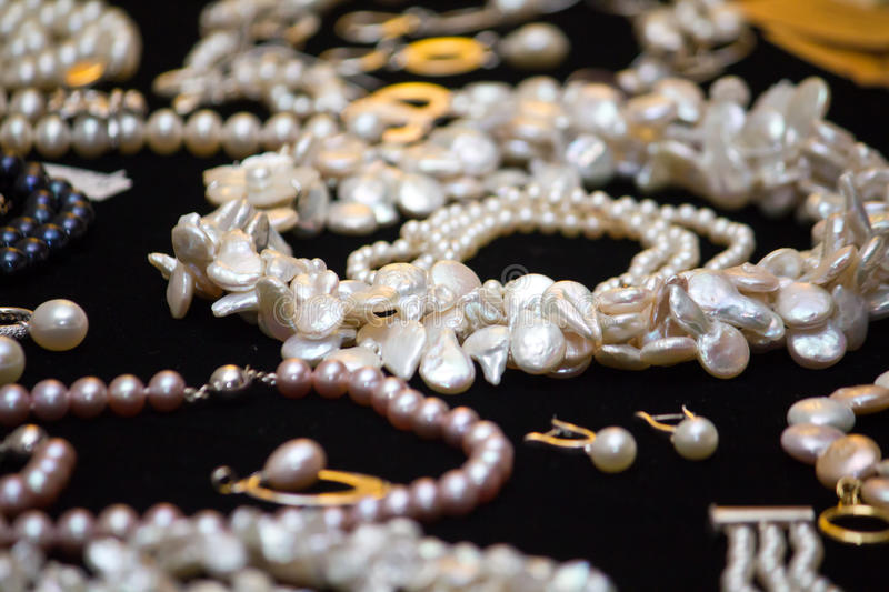 Jewelry. Pearl jewelry and earrings on black canvas royalty free stock photo
