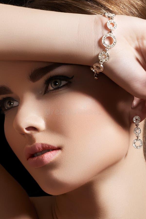 Jewelry accessories. Model with diamond bracelet. Beautiful woman model in retro style make-up. Accessories, jewelry gold bracelet and earrings with diamonds royalty free stock photos