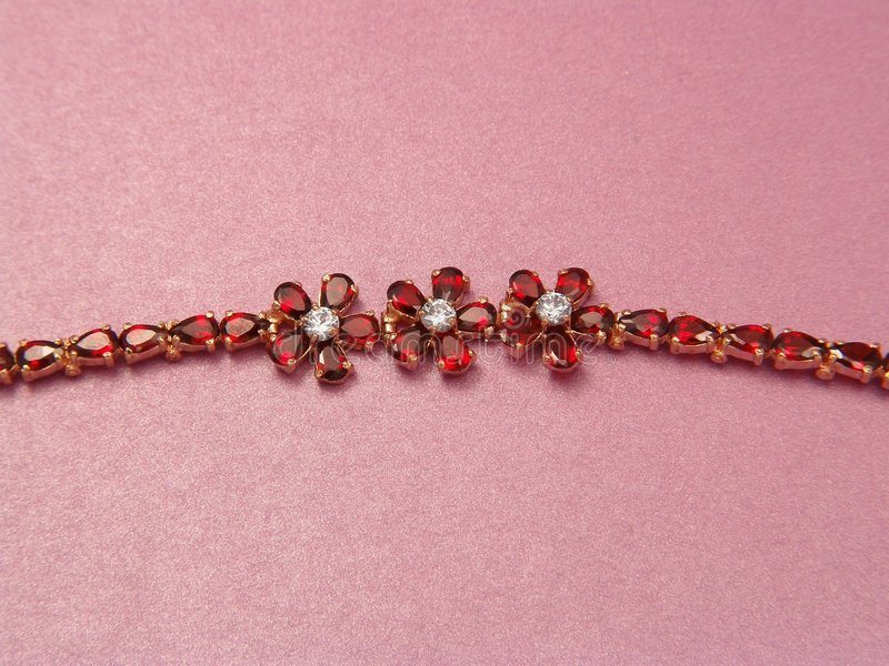 Jewelry bracelet with garnets. On pink background for Valentine & wedding cards stock photo