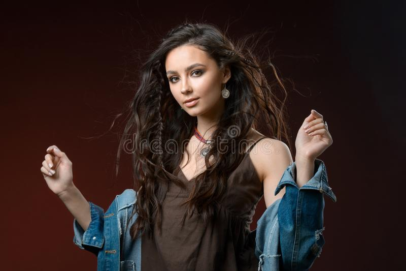 Jewelry concept. Beauty portrait of a beautiful female model posing isolated on brown background royalty free stock image