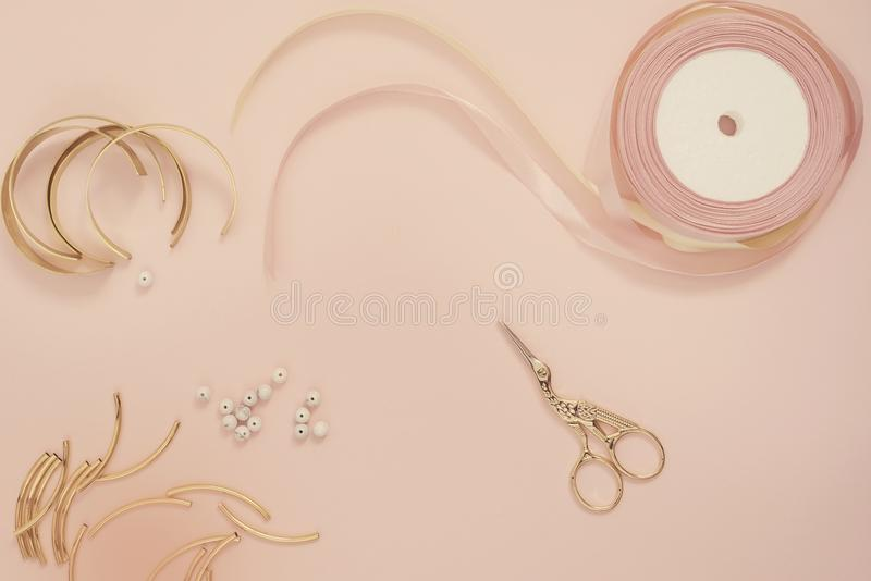 Jewelry designer workplace. Handmade, craft concept. Materials for making jewelry ? golden scissors, ribbons, gold tubes, bracelet stock images