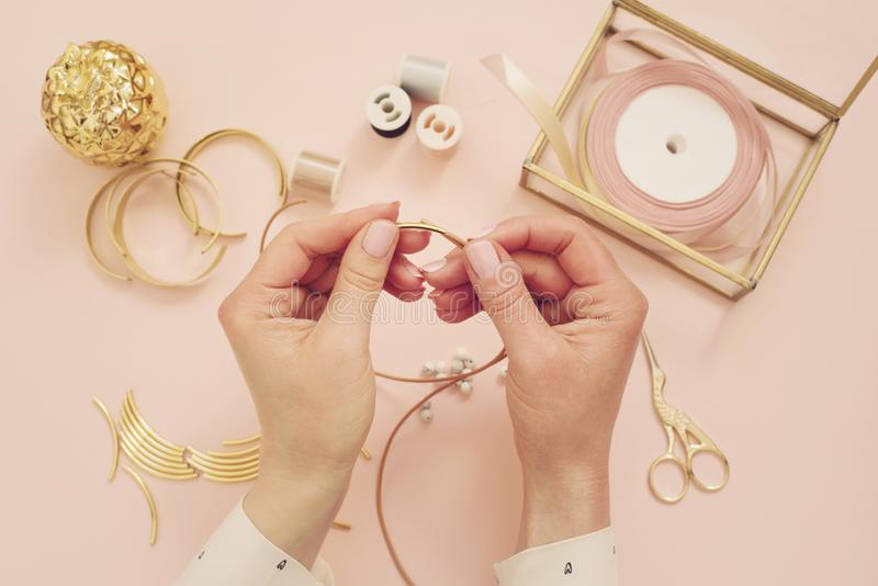 Jewelry designer workplace. Woman hands making handmade jewelry. Freelance fashion femininity workspace in flat lay style. Pastel royalty free stock image