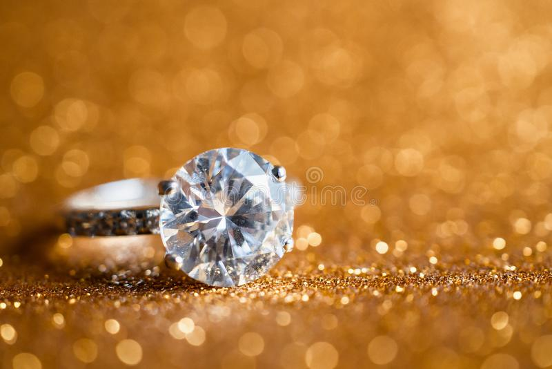 Jewelry diamond ring with abstract festive glitter Christmas holiday texture background. Blur with bokeh light royalty free stock photography