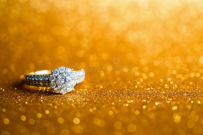 Jewelry diamond ring with abstract festive glitter Christmas holiday texture background. Blur with bokeh light stock photo