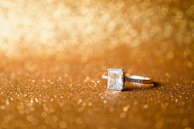 Jewelry diamond ring with abstract festive glitter Christmas holiday texture background. Blur with bokeh light royalty free stock image
