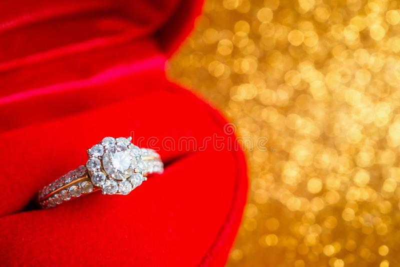 Jewelry diamond ring in gift box with abstract festive glitter Christmas holiday texture background. Blur with bokeh light royalty free stock images