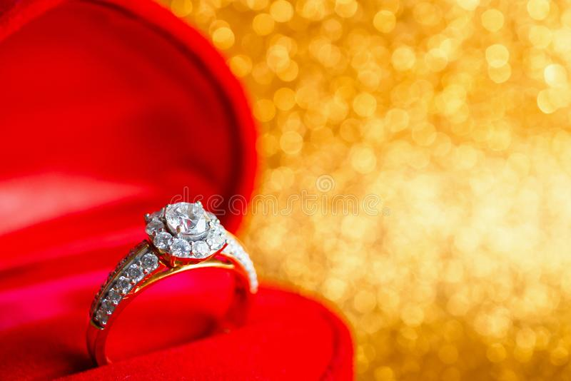 Jewelry diamond ring in gift box with abstract festive glitter Christmas holiday texture background. Blur with bokeh light stock images