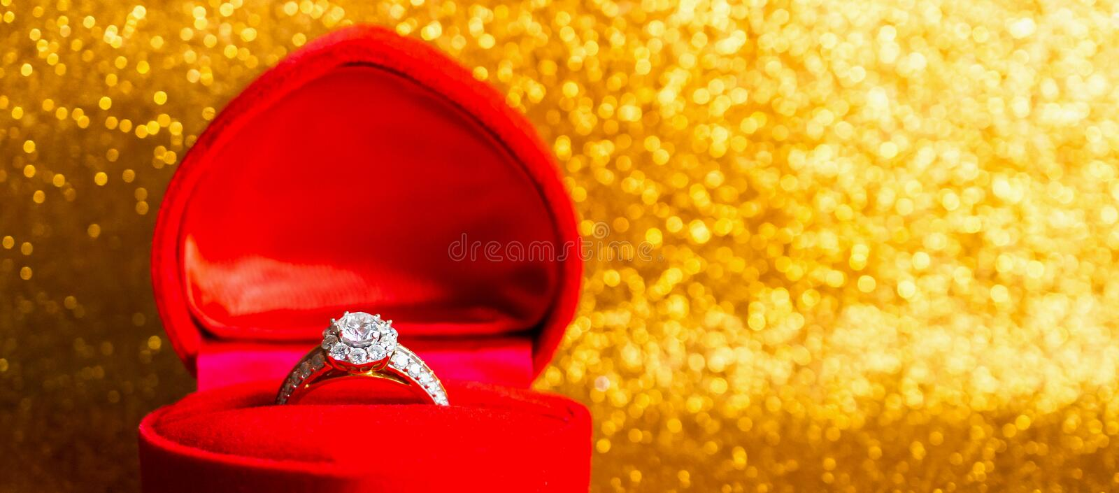 Jewelry diamond ring in gift box with abstract festive glitter Christmas holiday texture background. Blur with bokeh light royalty free stock image