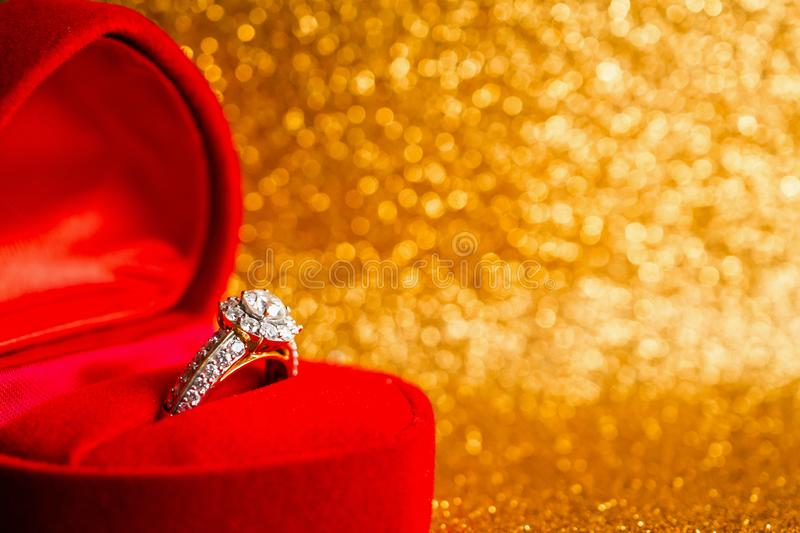 Jewelry diamond ring in gift box with abstract festive glitter Christmas holiday texture background. Blur with bokeh light royalty free stock photos