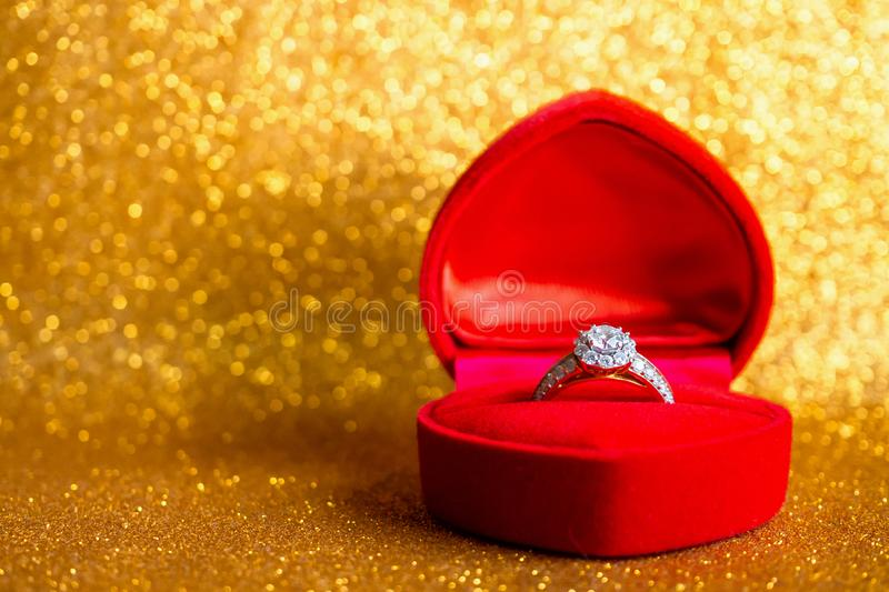 Jewelry diamond ring in gift box with abstract festive glitter Christmas holiday texture background. Blur with bokeh light stock image