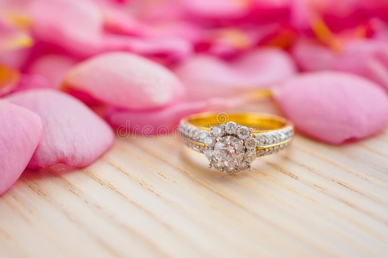 Jewelry diamond ring on wood table with beautiful pink rose petal background royalty free stock photo