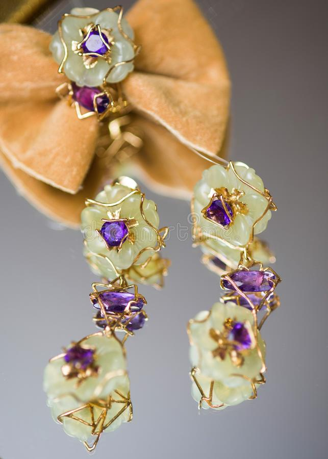 Jewelry, earrings and brooch on a mirror background. stock images