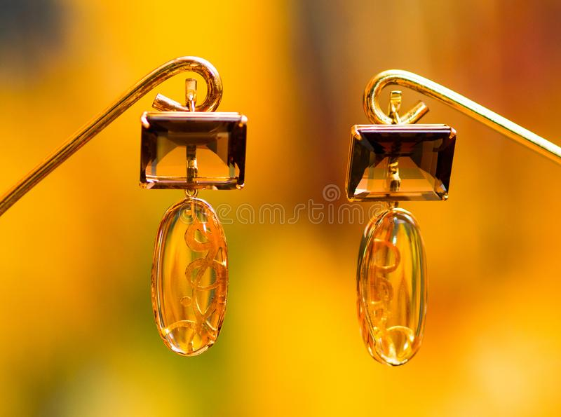 Jewelry, earrings on a blurred yellow background royalty free stock image