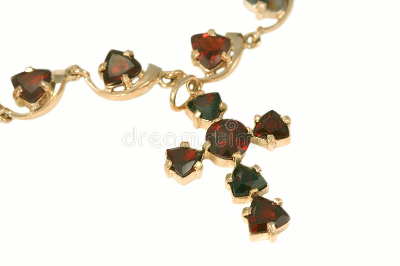 Jewelry with garnets. Golden jewelry Cross with garnets stock image