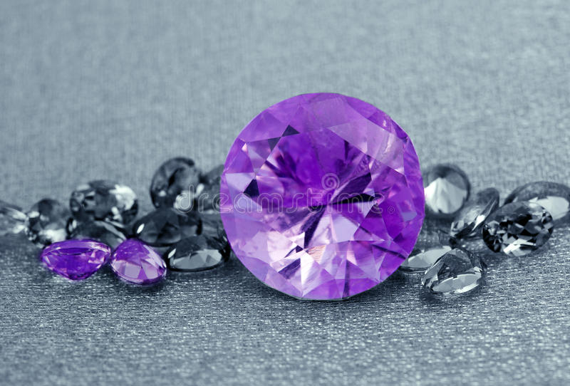 Jewelry gem stones. Various Jewelry gem stones amethyst on grey background royalty free stock images