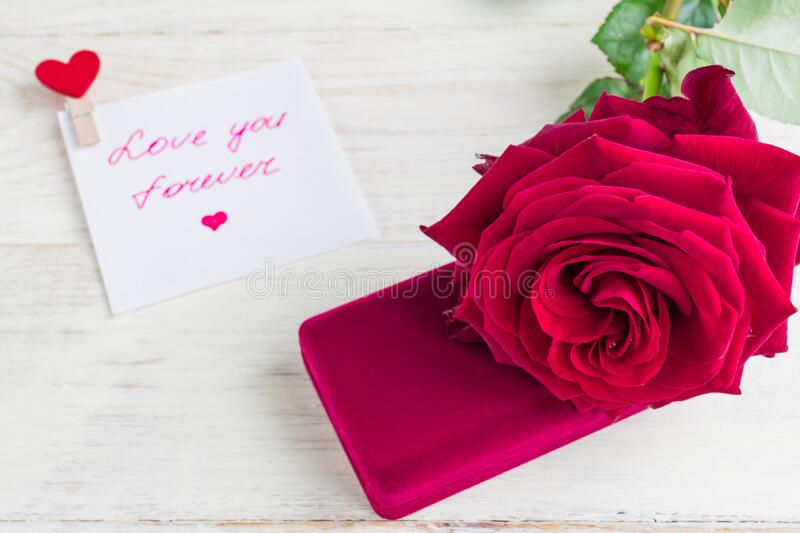 Jewelry gift box and bautiful red rose on wooden background stock photo