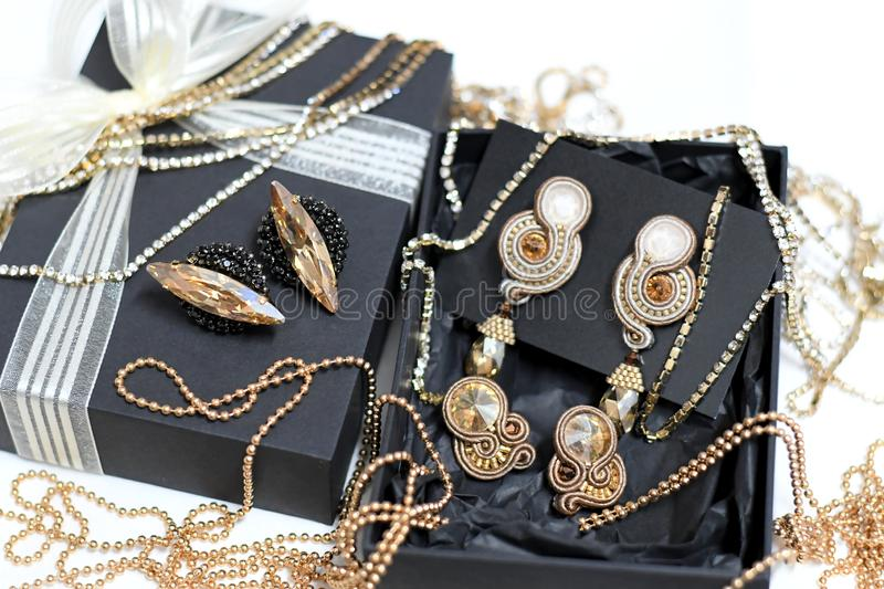 Jewelry gift box. Black gift box with jewelry earrings set in gold tone stock photos
