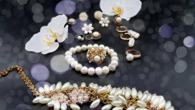 Jewelry gold white pearl  set  for woman and girl necklace earrings  bracelet   earring rings on black gold silver  backgroun. Beautiful jewelry white pearl  set stock photos