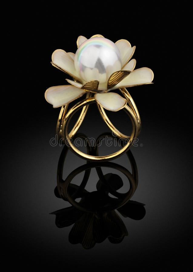 jewelry golden ring with pearl on black background with reflection stock photography