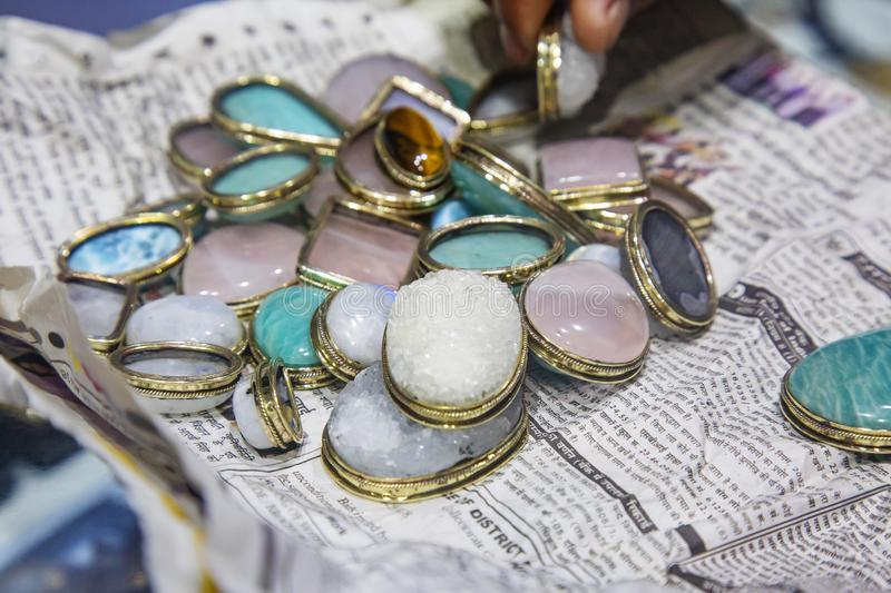 Jewelry; jewellery; jewel; gem; gemstone; genuine; mineral; oval; metal; frame; paper; newspaper; color; collection; bunch; many; royalty free stock photography