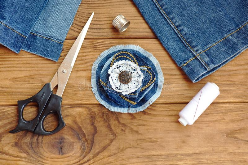 Blue jean flower brooch or hair accessory. Scissors, thread, thimble, needle, old jeans on a wooden table. Denim recycling idea. Jewelry made from denim. Cheap stock image