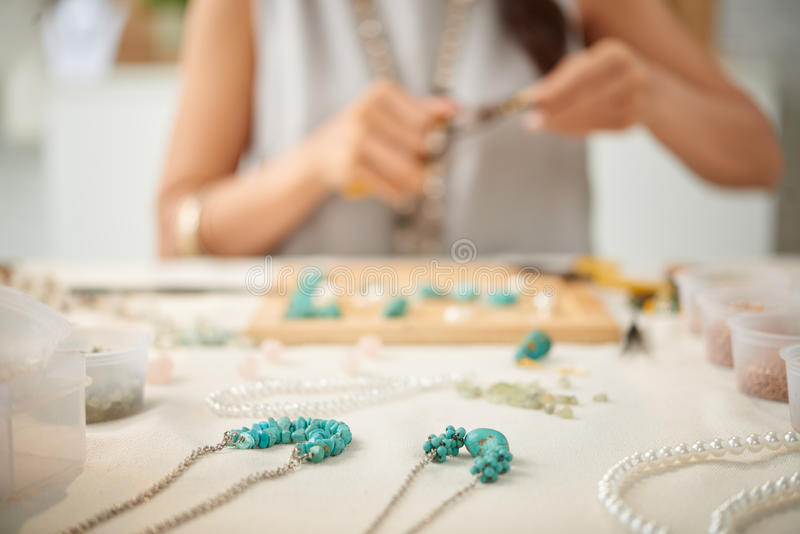 Jewelry maker. Woman creating her line of necklaces, selective focus stock images