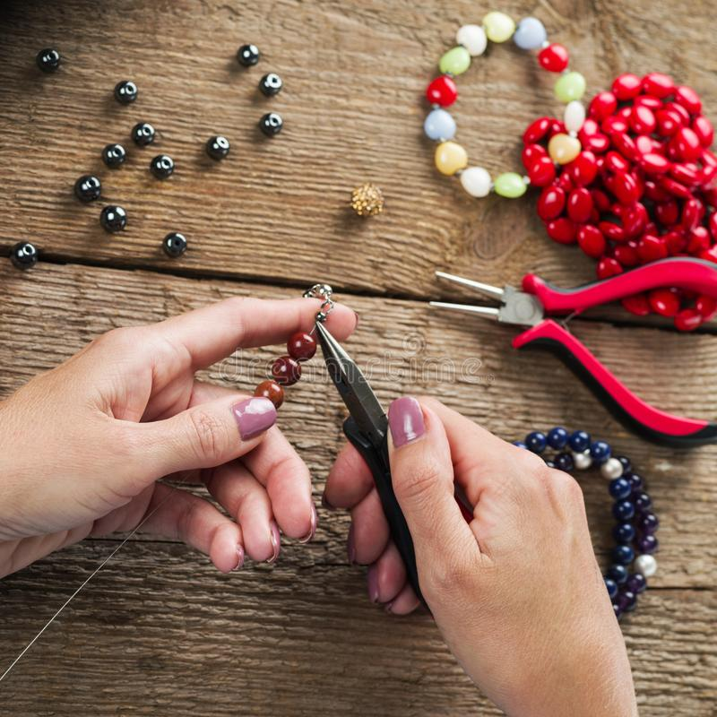 Jewelry making. Making bracelet of colorful beads. Female hands with a tool on a rough wooden table. Selective focus stock photos