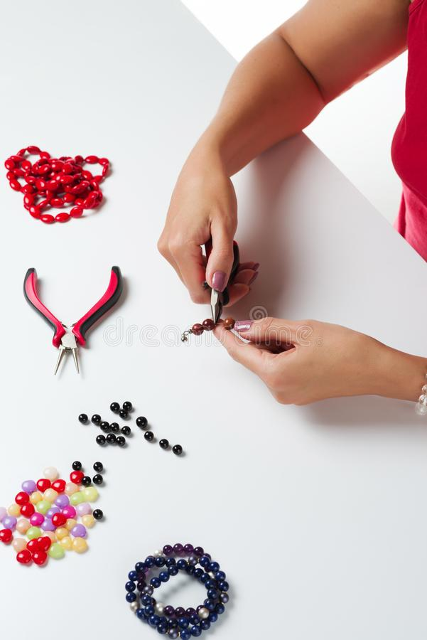 Jewelry making. Making bracelet of colorful beads. Female hands with a tool on a white. Background stock photography