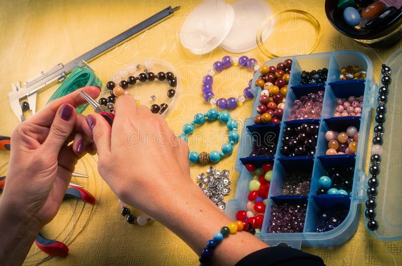 Jewelry making. Making bracelet of colorful beads. Female hands with a tool on a yellow background. stock images