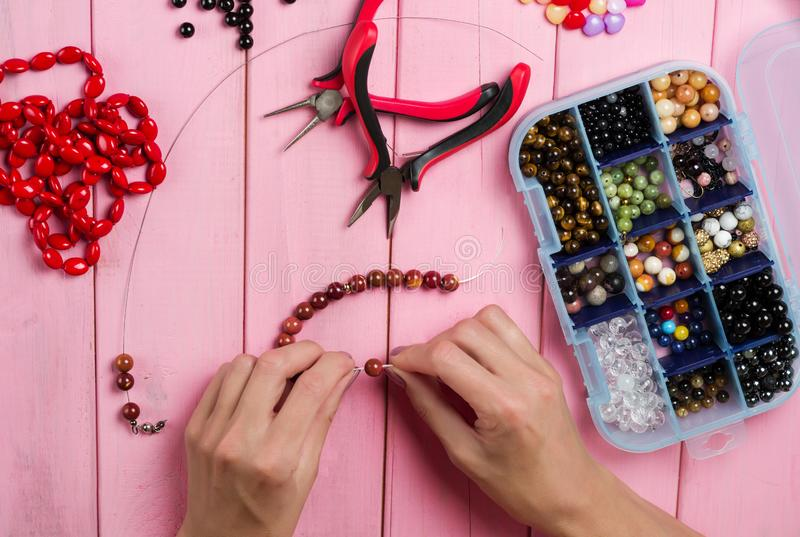 Jewelry making. Making bracelet of colorful beads. Female hands with a tool on a pink wooden table stock photography