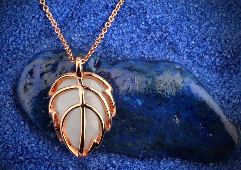 Jewelry pendant on dark blue sand background stock photo