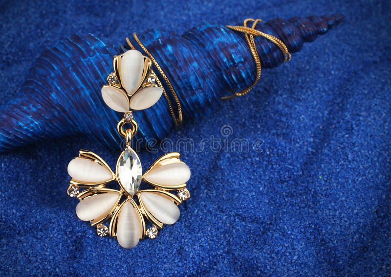 Jewelry pendant with nacre and diamonds on dark blue seashell ba royalty free stock images