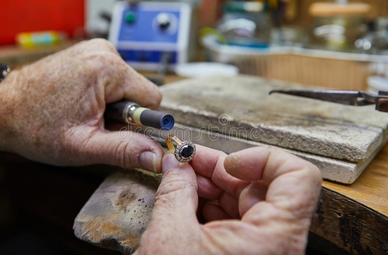 Jewelry production. Jeweler polishes a gold ring. On an old workbench in an authentic jewelry workshop royalty free stock photo