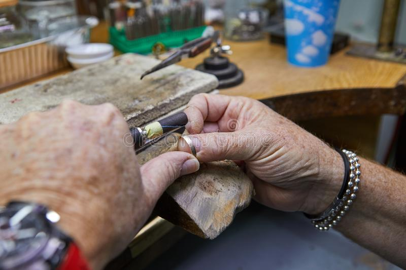 Jewelry production. Jeweler polishes a gold ring. On an old workbench stock photography