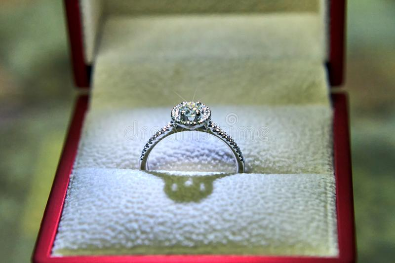 Jewelry production. White gold diamond ring in ice-lit gift box. Wedding, engagement, marriage proposal.  stock images