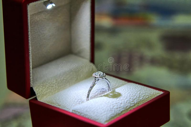 Jewelry production. White gold diamond ring in ice-lit gift box. Wedding, engagement, marriage proposal.  stock photos