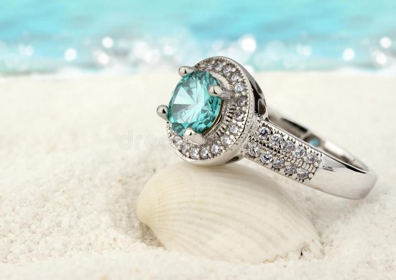 Jewelry ring with clean aquamarine gem on sand beach background stock image