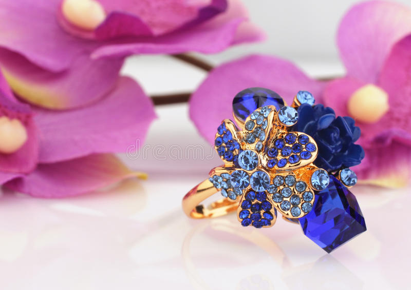 Jewelry ring with blue gems and flower background royalty free stock images