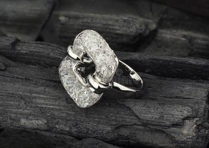 Jewelry ring with diamonds, on black coal texture background stock photography